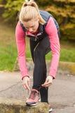 Mulher desportiva que amarra suas sapatas Fotos de Stock