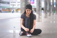 Mulher desportiva que amarra suas sapatas prontas para movimentar-se da cidade imagem de stock