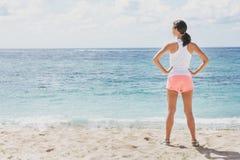 Mulher desportiva que aquece-se antes do exercício na praia fotografia de stock