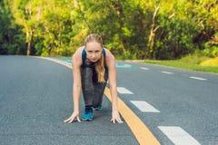 Mulher desportiva que corre na estrada no nascer do sol Conceito do bem-estar da aptidão e do exercício imagem de stock