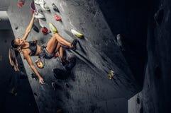 Mulher desportiva que escala o pedregulho artificial dentro imagens de stock