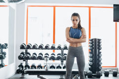 A mulher desportiva que está com braços cruzou-se no gym da aptidão fotografia de stock