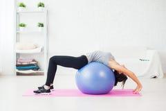 Mulher desportiva que faz esticando o exercício da aptidão sobre imagens de stock