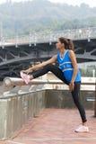 Mulher desportiva que faz estiramentos antes de exercitar no parque fotos de stock royalty free