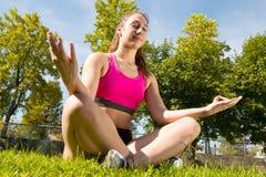 Mulher desportiva que faz a ioga no parque imagens de stock