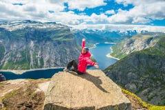 Mulher desportiva que levanta em Trolltunga Noruega Fotografia de Stock Royalty Free