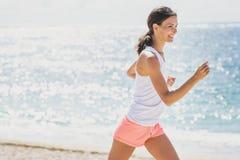 Mulher desportiva que movimenta-se com céus e mar no fundo fotos de stock royalty free
