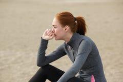 Mulher desportiva que senta-se fora e que relaxa após o exercício Imagens de Stock
