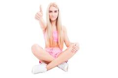 Mulher desportiva que senta-se na posição de lótus e que mostra como o gesto imagens de stock royalty free