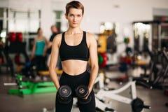 Mulher desportiva que veste no sportswear preto, pesos de levantamento do peso no gym fotografia de stock royalty free