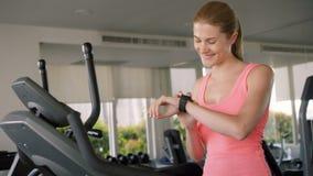 Mulher desportivo ativa apta que faz exercícios no velosimulator Usando seu smartwatch, mensagem com amigo filme