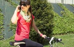 Mulher desportivo com bicicleta do fixie que chama pelo telefone imagens de stock royalty free