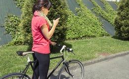 Mulher desportivo com a bicicleta do fixie que olha o smartphone fotografia de stock