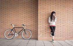 Mulher desportivo com bicicleta do fixie sobre uma parede de tijolo imagem de stock royalty free