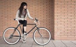 Mulher desportivo com bicicleta do fixie sobre uma parede de tijolo imagens de stock