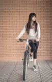 Mulher desportivo com bicicleta do fixie sobre uma parede de tijolo fotografia de stock