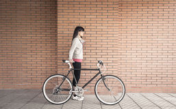 Mulher desportivo com bicicleta do fixie sobre uma parede de tijolo imagem de stock