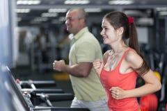 A mulher desportivo e o homem estão movimentando a escada rolante Imagem de Stock