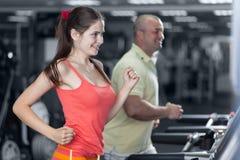 A mulher desportivo e o homem estão movimentando a escada rolante Imagens de Stock