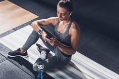 mulher desportivo nos fones de ouvido usando o smartphone ao descansar na esteira imagens de stock