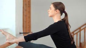 Mulher desportivo nova que estica os pés em um gym Menina bonita que faz um exercício do bailado vídeos de arquivo