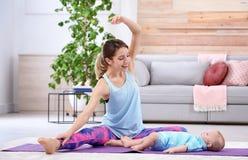 Mulher desportivo nova que faz o exercício com seu filho em casa imagem de stock