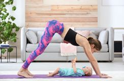 Mulher desportivo nova que faz o exercício com seu filho em casa imagens de stock royalty free