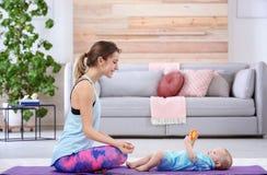 Mulher desportivo nova que faz o exercício com seu filho em casa, espaço para o texto fotografia de stock