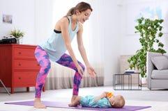 Mulher desportivo nova que faz o exercício com seu filho em casa, espaço para o texto fotos de stock