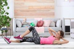 Mulher desportivo nova que faz o exercício quando seu filho que senta-se no sofá em casa fotos de stock royalty free