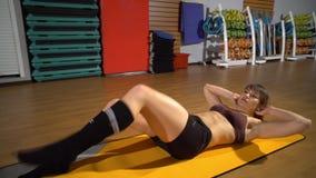 A mulher desportivo que faz o Abs exercita para ter a barriga lisa, treinando no clube de aptidão Ostenta mulheres bonitas no gym video estoque