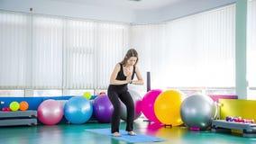 Mulher desportivo que toma a pose da cadeira no Gym filme