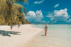 Mulher despreocupada bonita feliz que aprecia a luz do sol na praia Jovem mulher no biquini cor-de-rosa vermelho 'sexy' no Sandy  Imagem de Stock Royalty Free