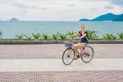 Mulher despreocupada com equitação da bicicleta pelo mar que tem o divertimento e o SMI fotos de stock royalty free