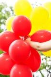 Mulher despreocupada, da liberdade com os balões vermelhos e amarelos Imagens de Stock Royalty Free