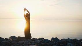 Mulher despreocupada na dança preta longa do vestido na praia no por do sol filme