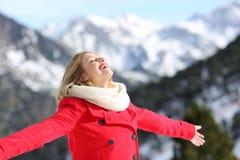 Mulher despreocupada que respira o ar fresco na montanha no inverno fotos de stock