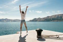 Mulher despreocupada que salta na praia Destino bonito do curso Porto de Baska, ilha de Krk, Croácia Foto de Stock