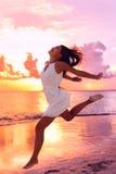 Mulher despreocupada que salta na praia durante o por do sol fotografia de stock royalty free