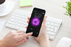 A mulher destrava o cinza do espaço do iPhone 6 sobre a tabela Foto de Stock Royalty Free