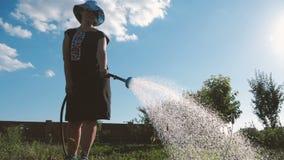 Mulher diligente em Panamá que molha seu jardim em um dia ensolarado no movimento lento vídeos de arquivo