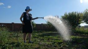 Mulher divertida que rega a água em seu jardim em um dia ensolarado no movimento lento video estoque