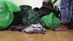 A mulher divide sua roupa em sacos de plástico video estoque