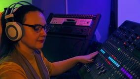 A mulher DJ nos fones de ouvido e nos vidros mistura trilhas para o disco em um console de mistura filme