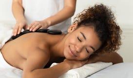 Mulher do Afro que aprecia a massagem de pedra quente, relaxando nos termas fotografia de stock
