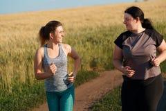Mulher do ajuste para motivar seu amigo em movimentar-se exterior foto de stock royalty free