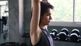 Mulher do ajuste que faz o exercício aéreo da extensão do tríceps com peso no gym video estoque