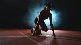 A mulher do atleta no short preto e um t-shirt nas sapatilhas estão nas almofadas running na trilha dos esportes complexos e video estoque