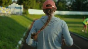 Mulher do atleta que espera no bloco começar na pista de atletismo 4k vídeos de arquivo
