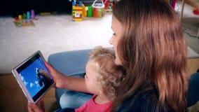 Mulher do baby-sitter com filme da família do relógio da menina da criança pequena na tela de tablet pc filme